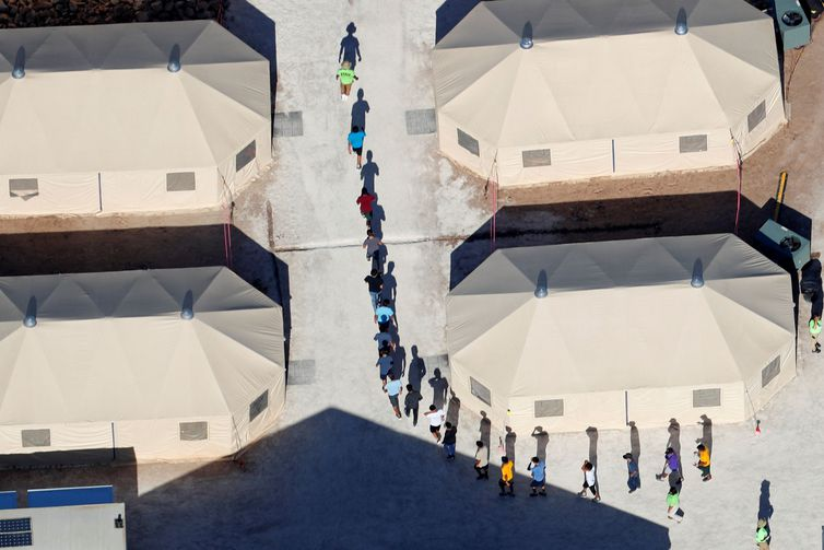 """Immigrant children, many of whom have been separated from their parents under a new """"zero tolerance"""" policy by the Trump administration, walk in single file between tents in their compound next to the Mexican border in Tornillo, Texas, U.S. June"""